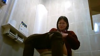 Asian women taking a leak in public toilet