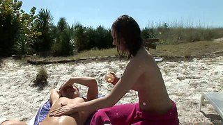 Two topless chicks is taking sun bath and smearing oil all over each others bodies