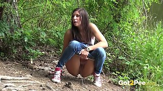 Shameless brunette chick enjoys pissing near a pond