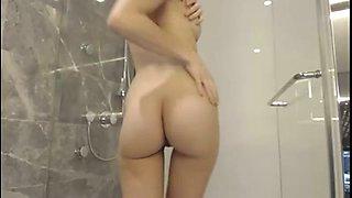 Cute brunette cam girl enjoys teasing herself in the shower