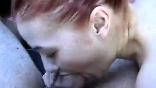 Redhead blows a small cock in the car