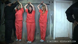 Three prisoners wearing orange suits are examined by their master in turn